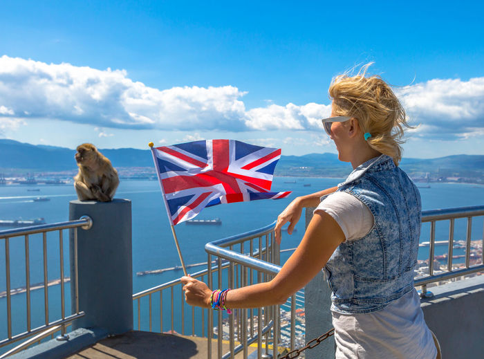 Woman With British Flag Standing By Monkey At Observation Point Against Blue Sky