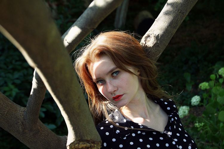 Portrait of beautiful young woman with tree