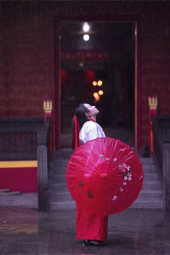 Woman with red umbrella standing outdoors during rainy season
