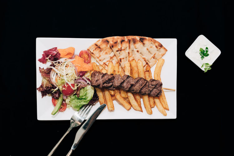 Greek souvlaki meal Beef Cuisine Fork Greek Knife Meal Salad Skewer Souvlaki Beef Souvlaki Food French Fries Greek Food Pita Bread Plate Suvlaki Tzatziki
