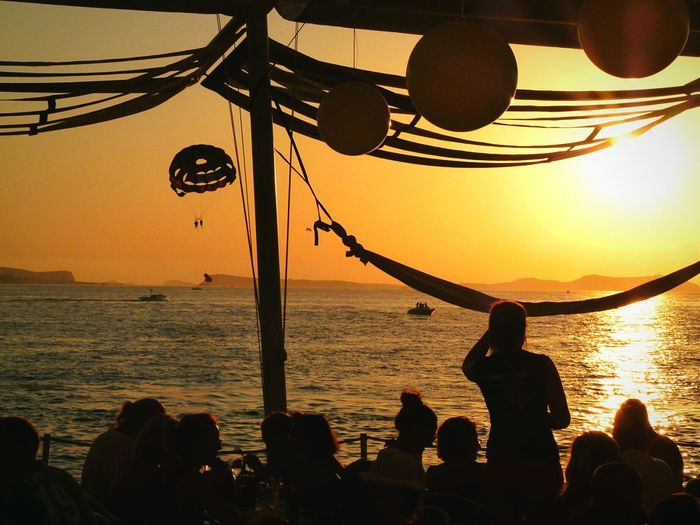 People At Outdoor Restaurant By Sea Against Orange Sky
