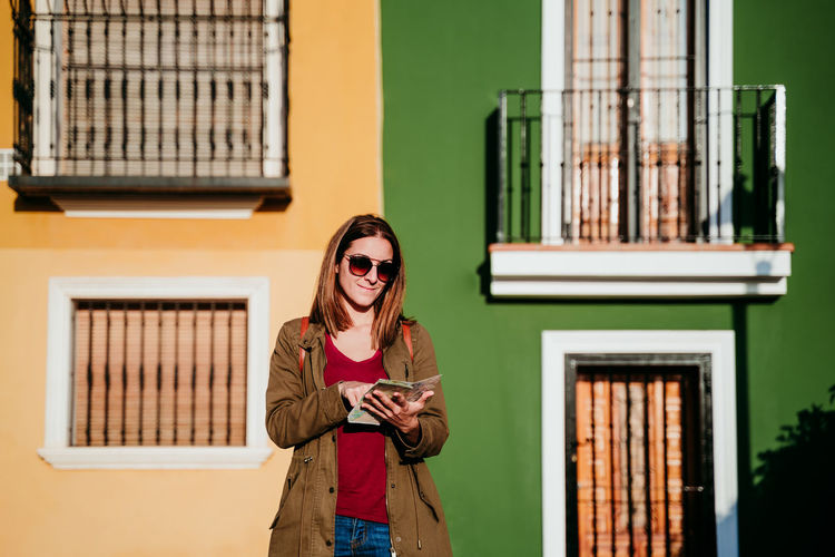 Smiling woman with map standing against wall during sunny day