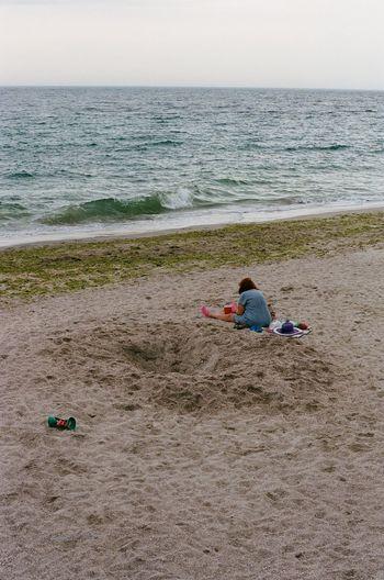 Rear view of siblings sitting on beach