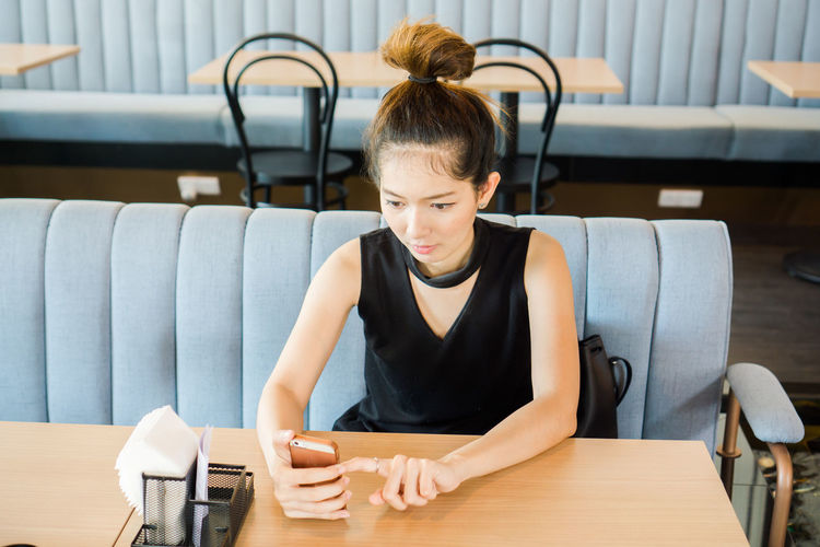 Young woman using phone on table at cafe
