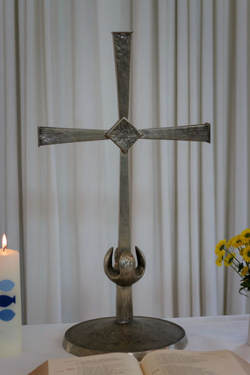 Small altar with holy cross, open bible, baptism candle and flowers in a vase Indoors  Religion Cross No People Belief Spirituality Home Interior Table Place Of Worship Decoration Curtain Shape Design Close-up Wood - Material Flower Metal Altar Baptism Flame Candle Bible Ceremony Christianity Preparation