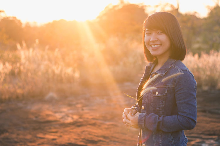 Portrait of smiling young woman outdoots during sunset