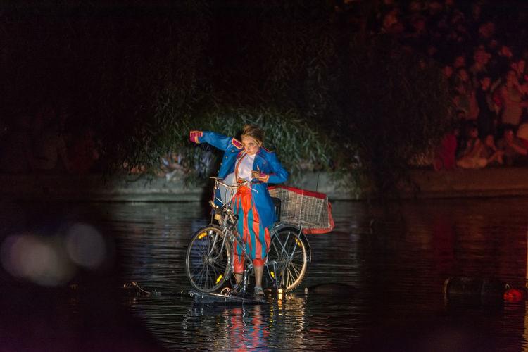 Man riding bicycle on river at night