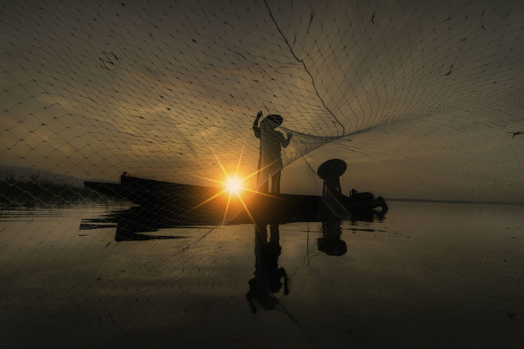 Men working on fishing net against sky during sunset