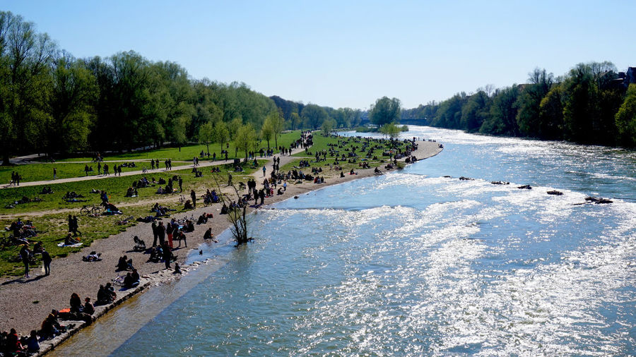 Group of people on riverbank against clear sky