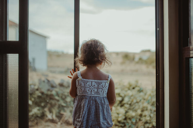 Rear view of girl standing by window at home