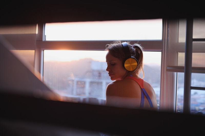 Rear view of woman listening music while sitting by window