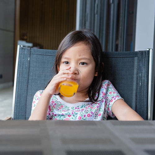 sitting cute little girl drinking orange juice Holding Hands Casual Clothing Child Childhood Drinking Females Food And Drink Front View Girl Girls Indoors  Leisure Activity Lifestyles One Person Orange Juice  Orange Juice In Glass Portrait Real People Sitting