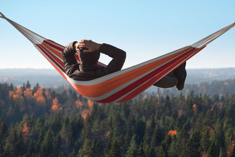 A man is lying on a hammock on a hill above a pine forest. His hands behind his head Leisure Activity One Person Nature Lifestyles Full Length Mid-air Day Sky Men Outdoors Land Mountain Man Lies Hammock Behind Hands HEAD Passivity Income Carelessness No Problems Slacker Lazy Hiking