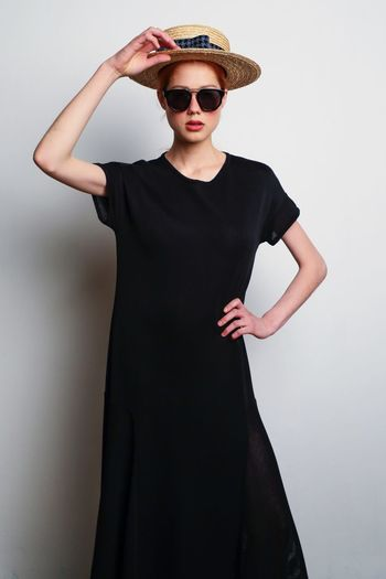Black is the new black Fashion Sunglasses Glasses Front View One Person Standing Young Adult Clothing Black Color Wall - Building Feature Young Women Lifestyles Indoors  Hand On Hip Portrait Real People Beautiful Woman Hand Three Quarter Length Adult