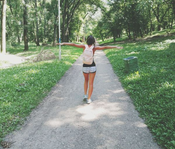Rear view full length of woman walking with arms outstretched in forest