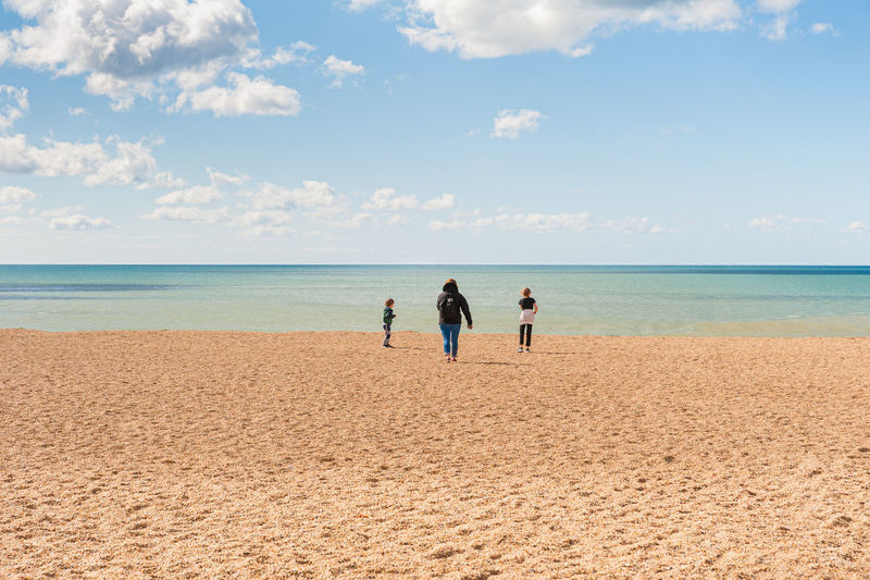 Rear view of mother and kids standing on beach against sky