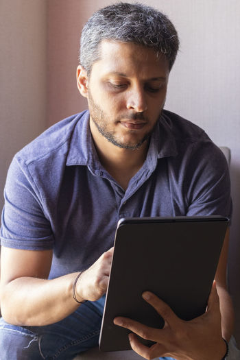 Mid adult man using mobile phone at home