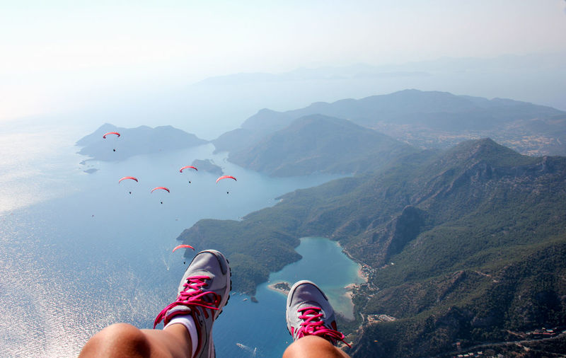 Low section of woman with people paragliding against sky