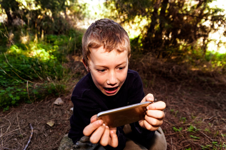 Portrait of smiling boy holding smart phone outdoors