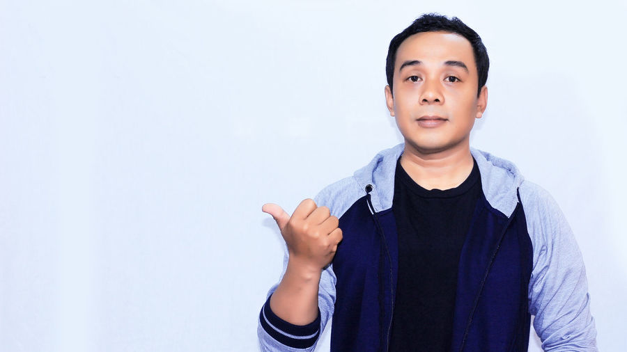 Portrait smile asian man with his gesture Looking At Camera Front View Casual Clothing Gesturing Portrait One Person Standing Indoors  White Background Waist Up Studio Shot Copy Space Lifestyles Child Men Males  Human Hand Wall - Building Feature Finger
