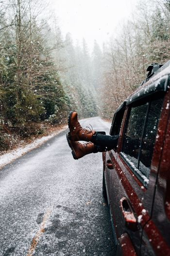 Low Section Of Person Removing Legs Through Car Window In Forest During Snowfall