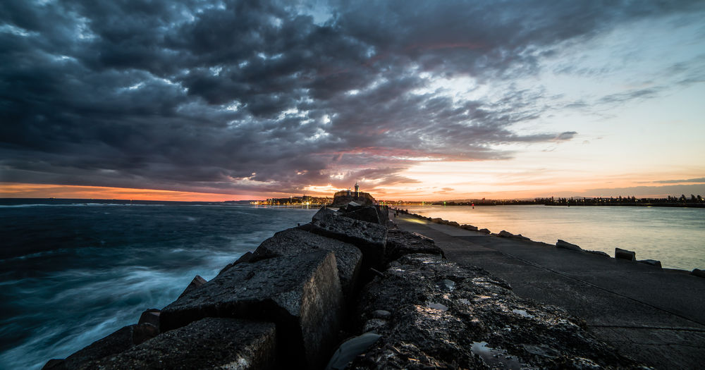 A storm rolling in over Newcastle break wall at sunset Break Wall Channel Harbour Light House Newcastle Upon Tyne Rock Rough Sea Storm Breakwall Breakwater Contrast Contrasts Dramatic Sky Gloomy Headland Long Exposure Ocean Outdoors Pacific Ocean Sea Smooth Storm Cloud Sunrise Sunset Tranquil Scene
