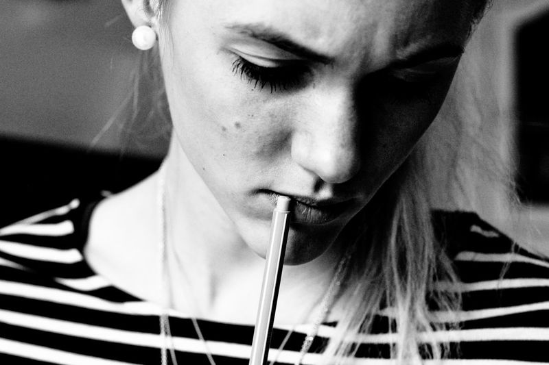 Close-up of woman touching lips with pen at home