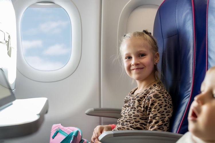 Portrait of happy boy sitting in airplane