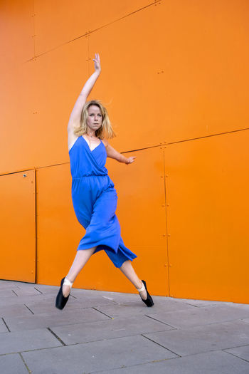 Full length of woman jumping against orange wall