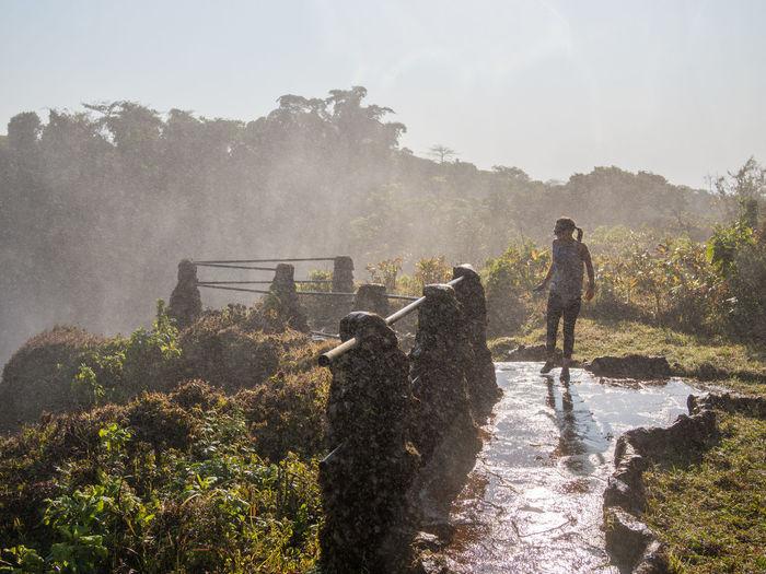 Woman walking on footpath with spray of lumangwe falls, zambia