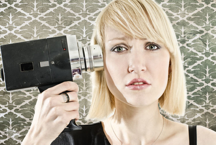 Portrait Of Woman Holding Video Camera Against Wall