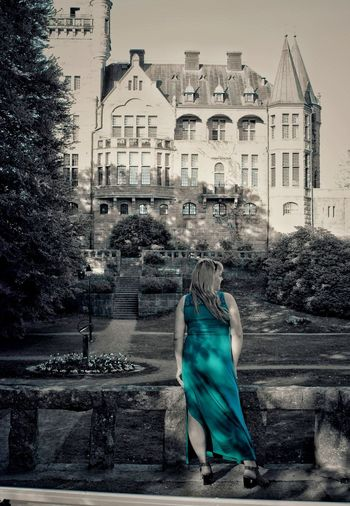 Woman standing by building in city