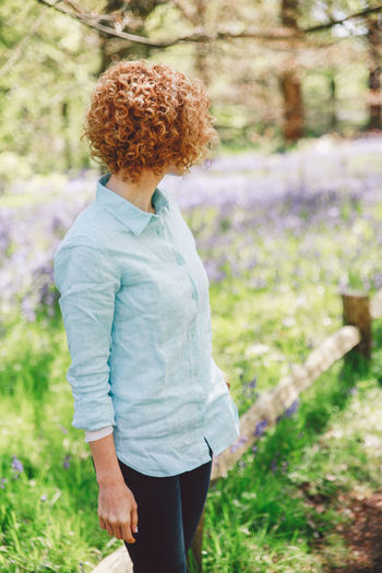 Woman standing by plants at forest