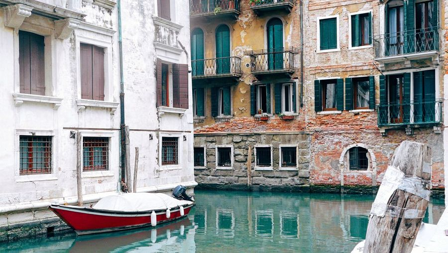 Rowboat moored in channel against old building