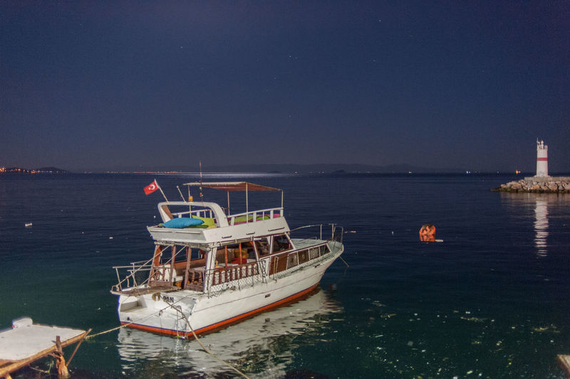 Boat moored on sea against clear sky at night