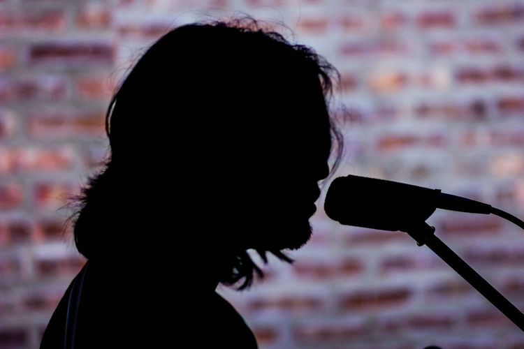 Side View Of Silhouette Singer By Microphone Against Brick Wall