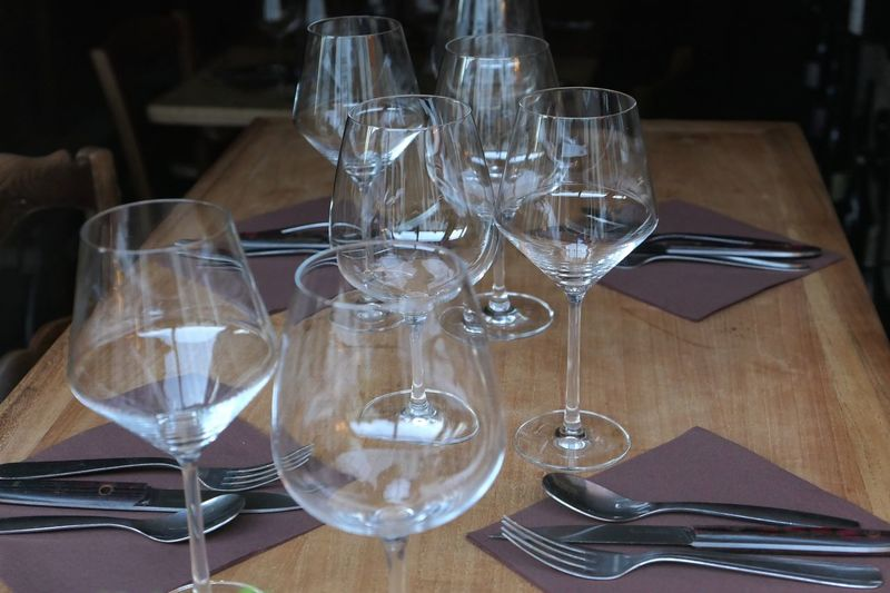 Close-up of empty wineglasses and place settings on table at restaurant