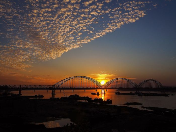 Silhouette Bridge Over River Against Cloudy Sky During Sunset