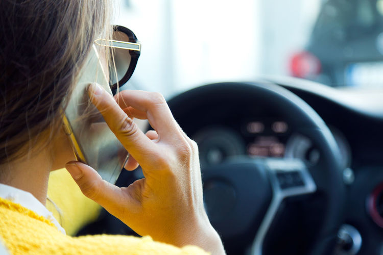 Woman talking on mobile phone while traveling in car