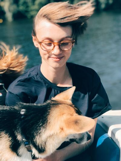 High Angle View Of Young Woman With Dog Sitting Against Lake