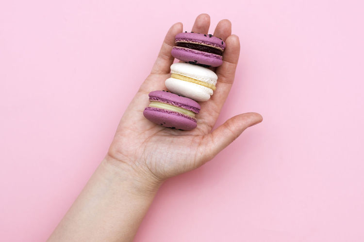 Cropped hand of woman holding macaroons over pink background