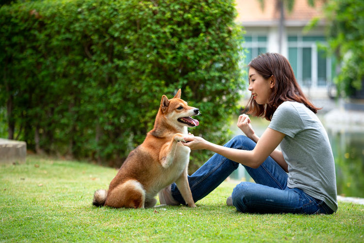 Woman with dog sitting on grass