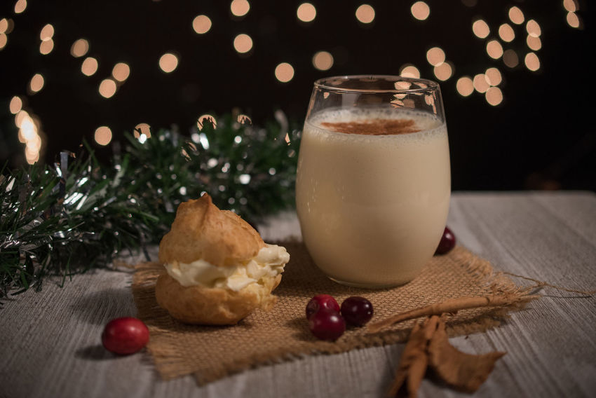 Egg nog and cream puff in a rustic setting Cream Puff Christmas Cinnamon Cranberries Drink Egg Nog Food And Drink Freshness Illuminated Milk No People Sweet Food Table