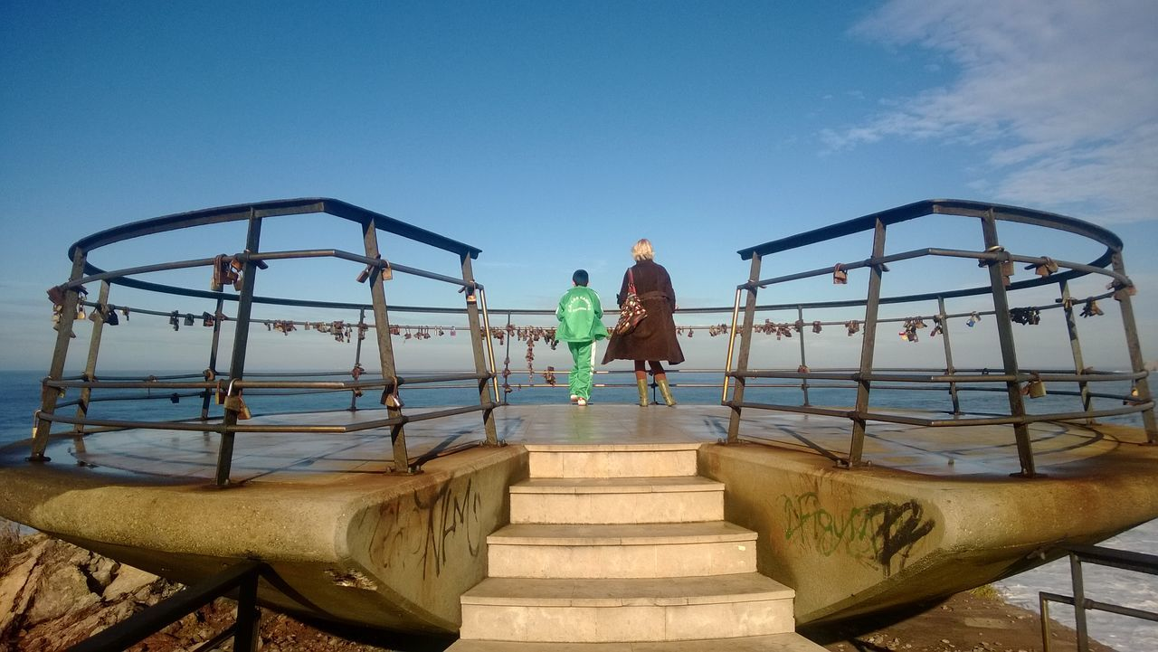 real people, full length, one person, childhood, leisure activity, steps, railing, day, rear view, outdoors, lifestyles, clear sky, sky, standing, sea, nature, climbing, men, hand rail, young adult