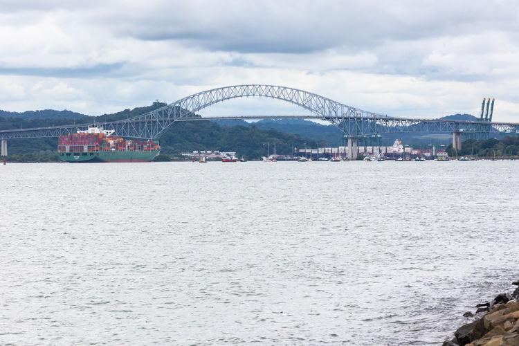 Arch bridge over sea against sky in city