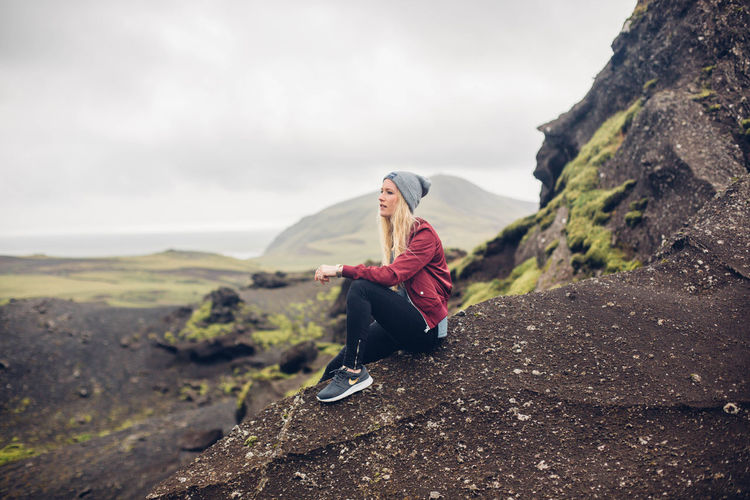 Woman sitting on rock against mountain