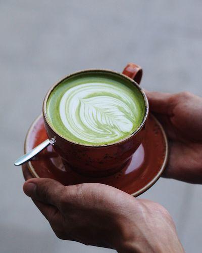 Close-up of hand holding matcha latte