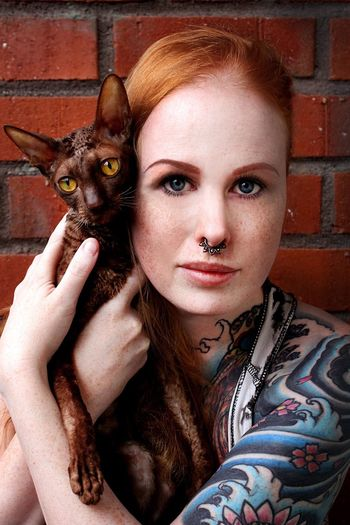Portrait of redhead woman holding cat against brick wall