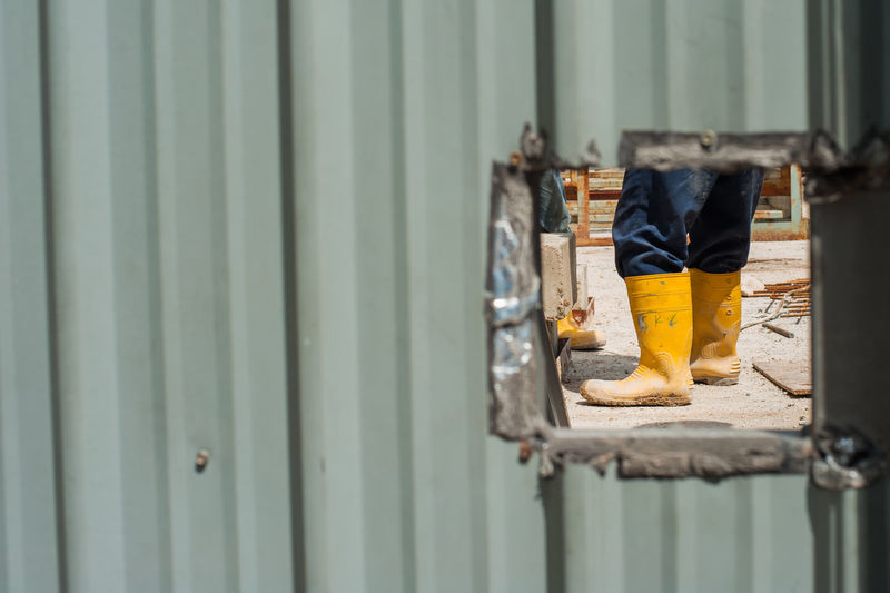 Low section of worker wearing yellow boots at construction site seen through hole