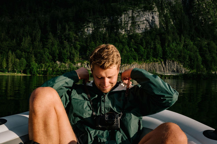 Young Man Sitting On Boat In Lake
